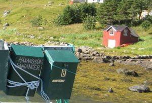 Grüne, schief hängende Postkästen in wilder, skandinavischer Landschaft.